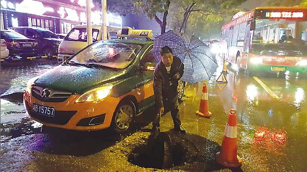 """""""井盖哥""""为守护行人安全站在雨中两小时"""